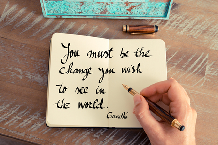 Retro effect and toned image of a woman hand writing on a notebook. Handwritten quote You Must Be The Change You  Wish To See In The World - Ghandi as inspirational concept image