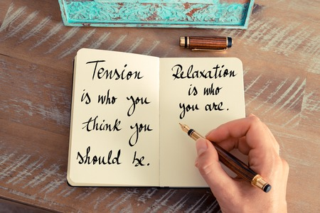 Retro effect and toned image of a woman hand writing on a notebook. Handwritten quote Tension is who you think you should be. Relaxation is who you are as inspirational concept image