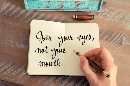 not open: Retro effect and toned image of a woman hand writing on a notebook. Handwritten quote Open your eyes, not your mouth as inspirational concept image