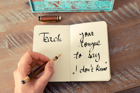 i dont know: Retro effect and toned image of a woman hand writing on a notebook. Handwritten quote Teach Your Tongue To Say I dont Know as inspirational concept image Stock Photo