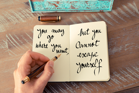 but think: Retro effect and toned image of a woman hand writing on a notebook. Handwritten quote You may go where you want, but you cannot escape yourself as inspirational concept image