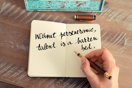 perseverance: Retro effect and toned image of a woman hand writing on a notebook. Handwritten quote Without perseverance talent is a barren bed as inspirational concept image