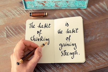 habit: Retro effect and toned image of a woman hand writing on a notebook. Handwritten quote The habit of thinking is the habit of gaining strength as inspirational concept image