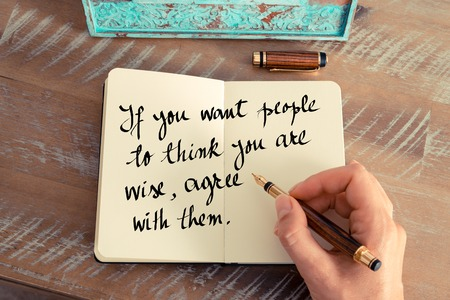 them: Retro effect and toned image of a woman hand writing on a notebook. Handwritten quote If you want people to think you are wise, agree with them as inspirational concept image Stock Photo