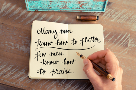 praise: Retro effect and toned image of a woman hand writing on a notebook. Handwritten quote Many men know how to flatter, few men know how to praise as inspirational concept image