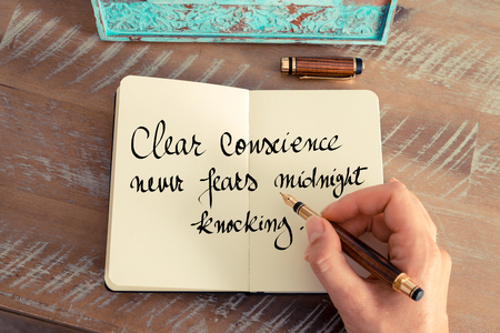 conscience: Retro effect and toned image of a woman hand writing on a notebook. Handwritten quote Clear conscience never fears midnight knocking as inspirational concept image Stock Photo