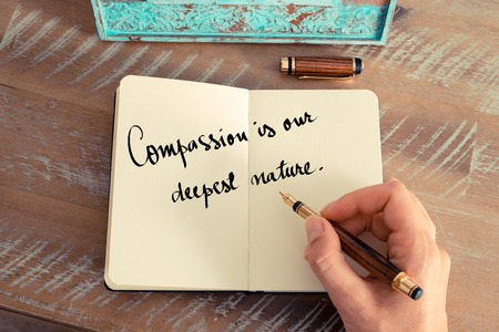 the deepest: Retro effect and toned image of a woman hand writing on a notebook. Handwritten quote Compassion is our deepest nature as inspirational concept image