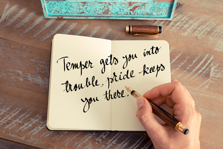 temper: Retro effect and toned image of a woman hand writing on a notebook. Handwritten quote Temper gets you into trouble, pride keeps you there as inspirational concept image Stock Photo