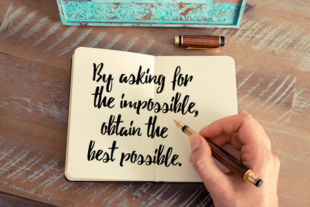 obtain: Retro effect and toned image of a woman hand writing on a notebook. Handwritten quote By asking for the impossible, obtain the best possible as inspirational concept image