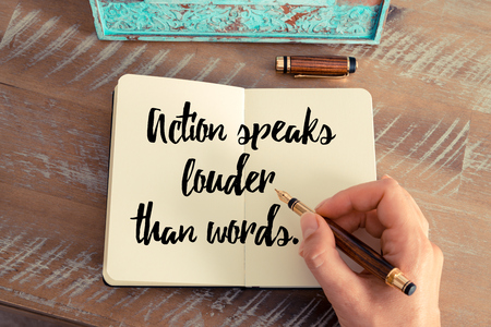 louder: Retro effect and toned image of a woman hand writing on a notebook. Handwritten quote Action speaks louder than words as inspirational concept image