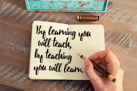 teach: Retro effect and toned image of a woman hand writing on a notebook. Handwritten quote By learning you will teach, by teaching you will learn.  as inspirational concept image