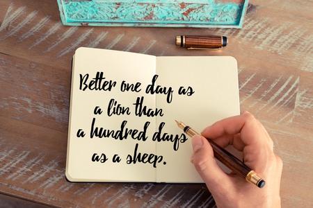 better days: Retro effect and toned image of a woman hand writing on a notebook. Handwritten quote Better one day as a lion than a hundred days as a sheep as inspirational concept image
