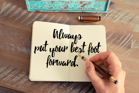 put forward: Retro effect and toned image of a woman hand writing on a notebook. Handwritten quote Always put your best foot forward as inspirational concept image Stock Photo