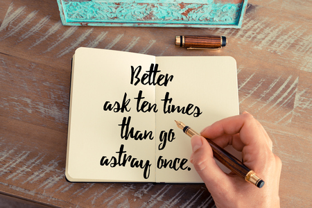 astray: Retro effect and toned image of a woman hand writing on a notebook. Handwritten quote Better ask ten times than go astray once as inspirational concept image Stock Photo