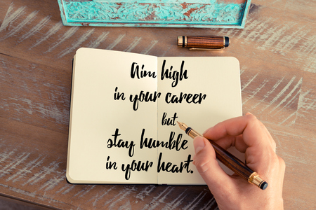 but think: Retro effect and toned image of a woman hand writing on a notebook. Handwritten quote Aim high in your career but stay humble in your heart as inspirational concept image