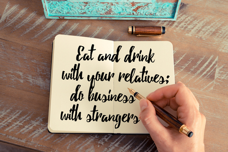 strangers: Retro effect and toned image of a woman hand writing on a notebook. Handwritten quote Eat and drink with your relatives; do business with strangers as inspirational concept image Stock Photo
