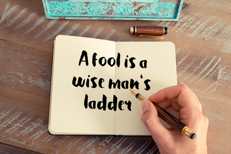 wise woman: Retro effect and toned image of a woman hand writing on a notebook. Handwritten quote A fool is a wise mans ladder as inspirational concept image