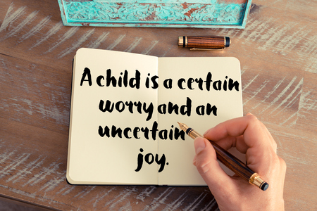 uncertain: Retro effect and toned image of a woman hand writing on a notebook. Handwritten quote A child is a certain worry and an uncertain joy as inspirational concept image