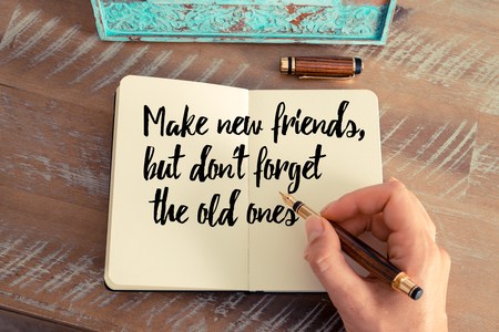 but think: Retro effect and toned image of a woman hand writing on a notebook. Handwritten quote Make new friends, but dont forget the old ones as inspirational concept image Stock Photo