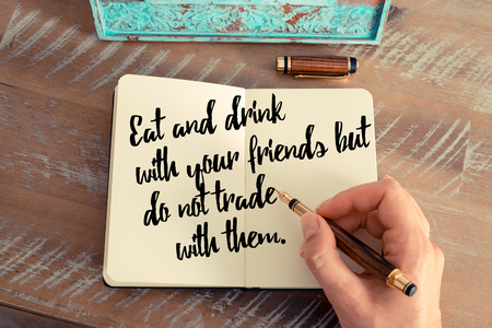 them: Retro effect and toned image of a woman hand writing on a notebook. Handwritten quote Eat and drink with your friends but do not trade with them as inspirational concept image
