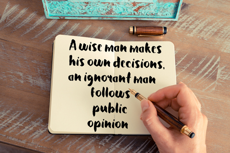 ignorant: Retro effect and toned image of a woman hand writing on a notebook. Handwritten quote A wise man makes his own decisions, an ignorant man follows public opinion as inspirational concept image