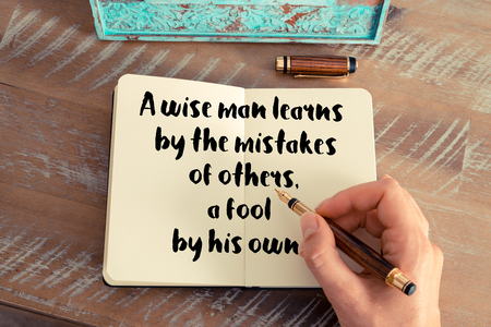 learns: Retro effect and toned image of a woman hand writing on a notebook. Handwritten quote A wise man learns by the mistakes of others, a fool by his own as inspirational concept image