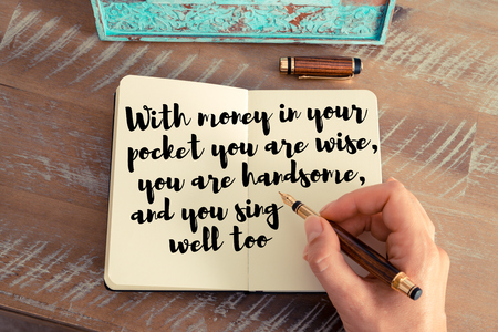wise woman: Retro effect and toned image of a woman hand writing on a notebook. Handwritten quote With money in your pocket you are wise, you are handsome, and you sing well too as inspirational concept image Stock Photo