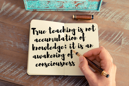 accumulation: Retro effect and toned image of a woman hand writing on a notebook. Handwritten quote True teaching is not accumulation of knowledge; it is an awakening of consciousness as inspirational concept image
