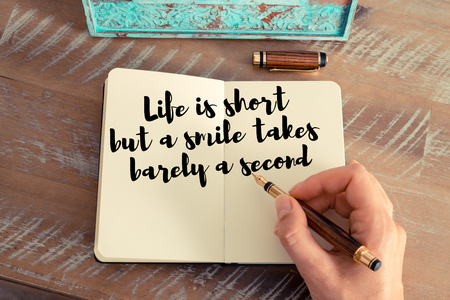 but think: Retro effect and toned image of a woman hand writing on a notebook. Handwritten quote Life is short but a smile takes barely a second as inspirational concept image