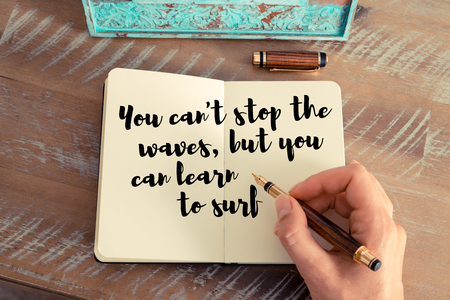 but think: Retro effect and toned image of a woman hand writing on a notebook. Handwritten quote You cant stop the waves, but you can learn to surf as inspirational concept image