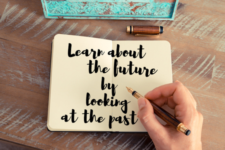 Retro effect and toned image of a woman hand writing on a notebook. Handwritten quote Learn about the future by looking at the past as inspirational concept image Stock Photo