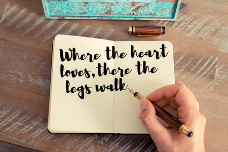 loves: Retro effect and toned image of a woman hand writing on a notebook. Handwritten quote Where the heart loves, there the legs walk as inspirational concept image Stock Photo