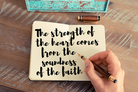 soundness: Retro effect and toned image of a woman hand writing on a notebook. Handwritten quote The strength of the heart comes from the soundness of the faith as inspirational concept image