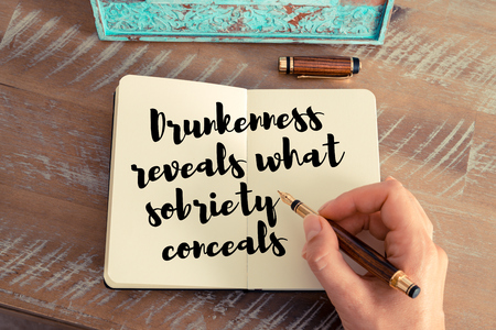 drunkenness: Retro effect and toned image of a woman hand writing on a notebook. Handwritten quote Drunkenness reveals what sobriety conceals as inspirational concept image Stock Photo