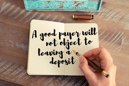 payer: Retro effect and toned image of a woman hand writing on a notebook. Handwritten quote A good payer will not object to leaving a deposit as inspirational concept image Stock Photo