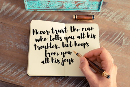 but think: Retro effect and toned image of a woman hand writing on a notebook. Handwritten quote Never trust the man who tells you all his troubles, but keeps from you all his joys as inspirational concept image