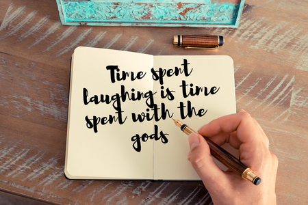 personal god: Retro effect and toned image of a woman hand writing on a notebook. Handwritten quote Time spent laughing is time spent with the gods as inspirational concept image