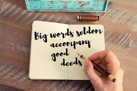 seldom: Retro effect and toned image of a woman hand writing on a notebook. Handwritten quote Big words seldom accompany good deeds as inspirational concept image
