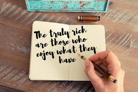 they: Retro effect and toned image of a woman hand writing on a notebook. Handwritten quote The truly rich are those who enjoy what they have as inspirational concept image Stock Photo
