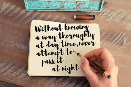knowing: Retro effect and toned image of a woman hand writing on a notebook. Handwritten quote Without knowing a way thoroughly at day time, never attempt to pass it at night as inspirational concept image
