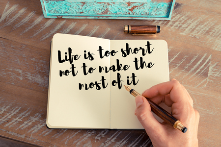 most creative: Retro effect and toned image of a woman hand writing on a notebook. Handwritten quote Life is too short not to make the most of it as inspirational concept image Stock Photo