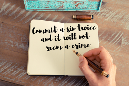 twice: Retro effect and toned image of a woman hand writing on a notebook. Handwritten quote Commit a sin twice and it will not seem a crime as inspirational concept image Stock Photo