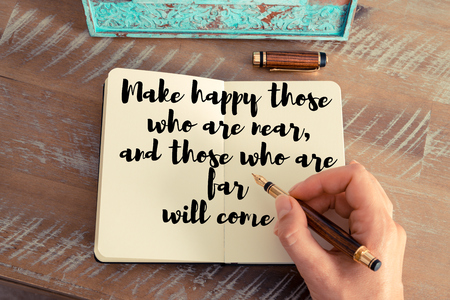 those: Retro effect and toned image of a woman hand writing on a notebook. Handwritten quote Make happy those who are near, and those who are far will come as inspirational concept image