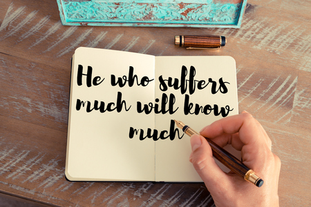 he: Retro effect and toned image of a woman hand writing on a notebook. Handwritten quote He who suffers much will know much as inspirational concept image