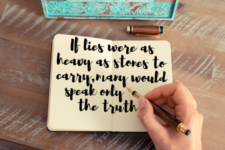 Retro effect and toned image of a woman hand writing on a notebook. Handwritten quote If lies were as heavy as stones to carry, many would speak only the truth as inspirational concept image Stock Photo