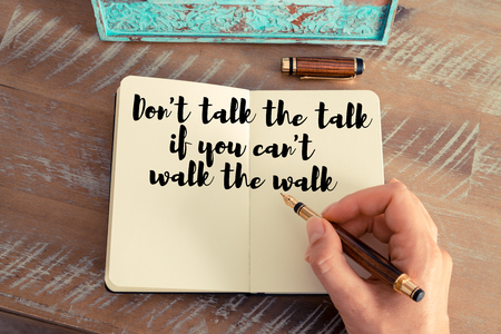 Retro effect and toned image of a woman hand writing on a notebook. Handwritten quote Don't talk the talk if you can't walk the walk as inspirational concept image