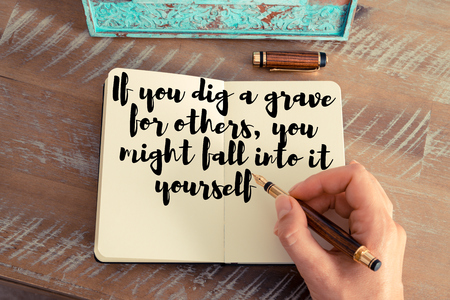 caes: Retro effect and toned image of a woman hand writing on a notebook. Handwritten quote If you dig a grave for others, you might fall into it yourself as inspirational concept image