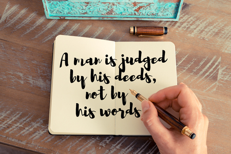 deeds: Retro effect and toned image of a woman hand writing on a notebook. Handwritten quote A man is judged by his deeds, not by his words as inspirational concept image Stock Photo