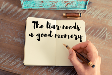 Retro effect and toned image of a woman hand writing on a notebook. Handwritten quote The liar needs a good memory as inspirational concept image