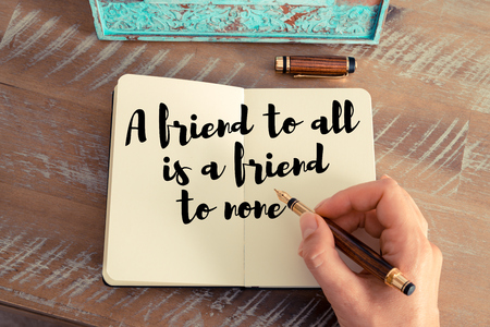none: Retro effect and toned image of a woman hand writing on a notebook. Handwritten quote A friend to all is a friend to none as inspirational concept image